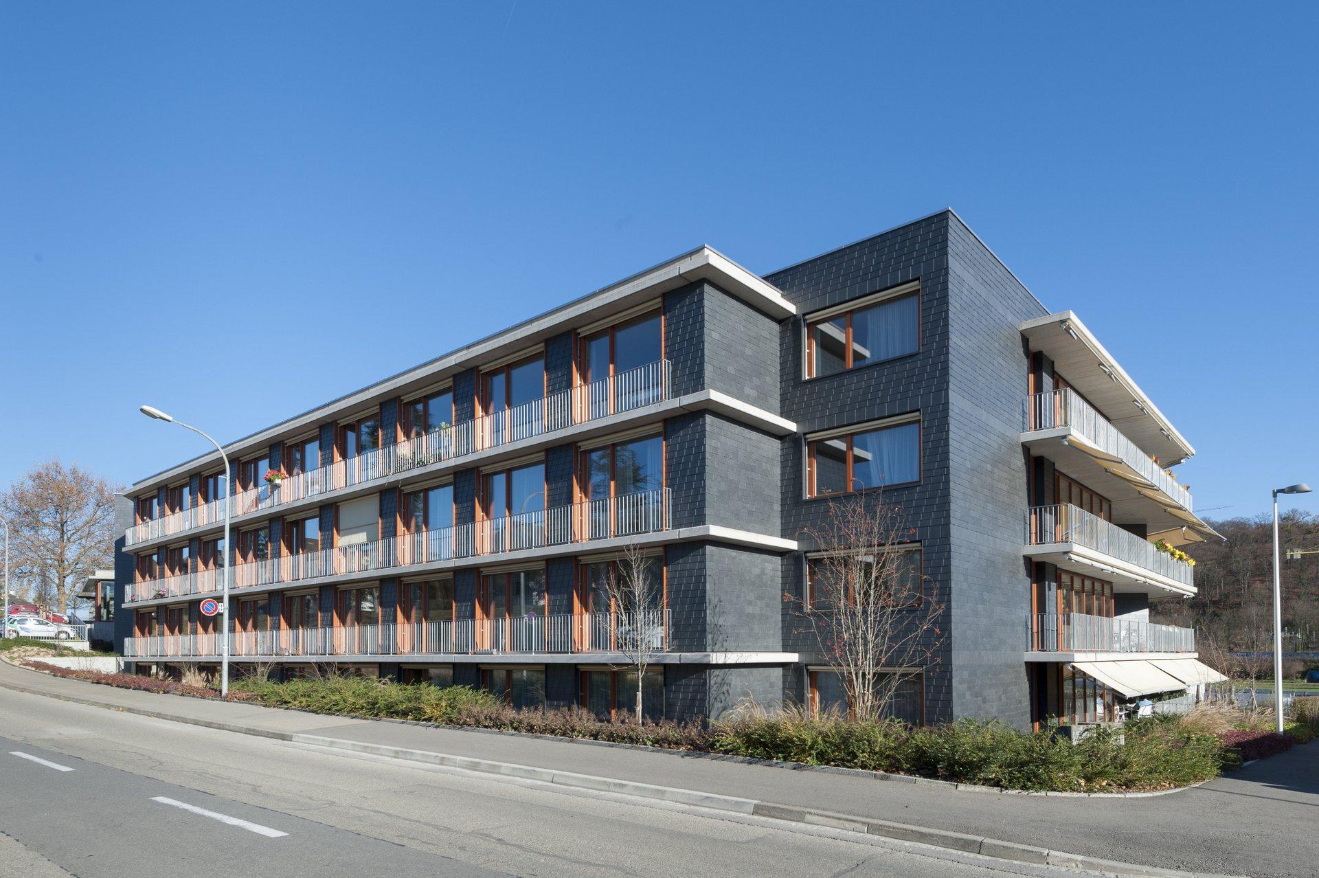 Mehrgeschossiges Wohngebäude mit gleichmässiger Fensteranordnung in Naturholz