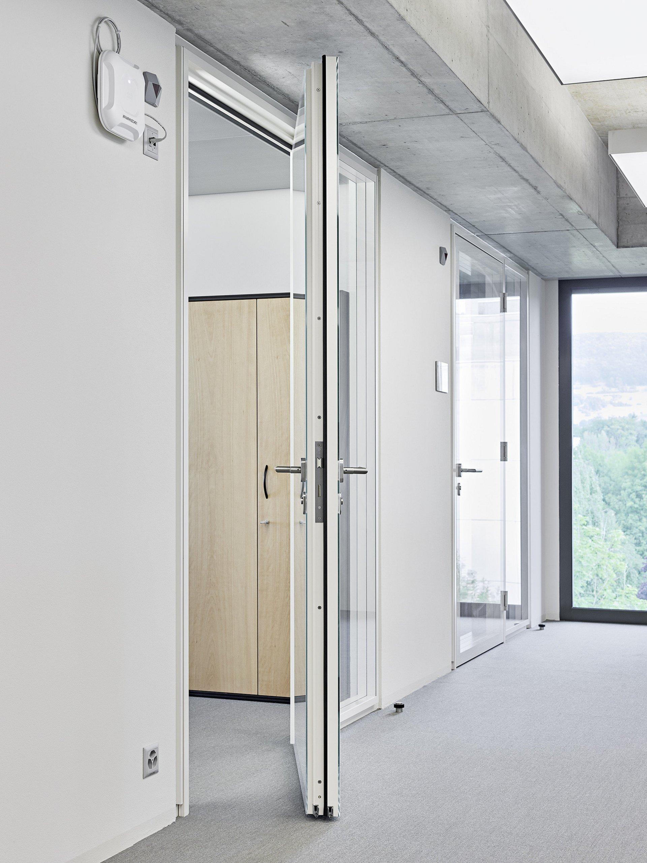 Flur mit 2 Glastüren, eine davon als Brandschutztür offen stehend