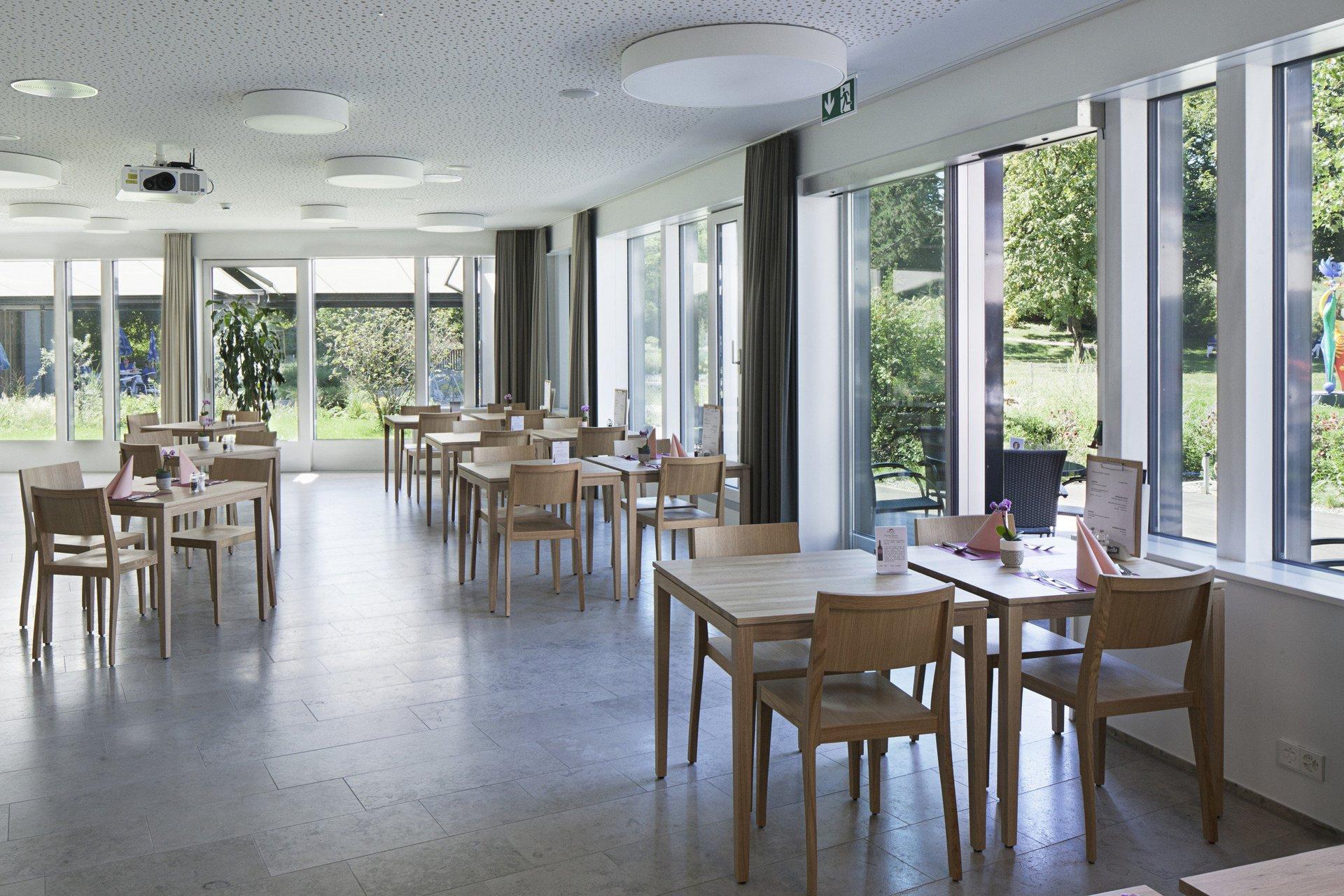 bestuhlter Aufenthaltsbereich mit grossen Holz-Metall-Schiebefensterelemente