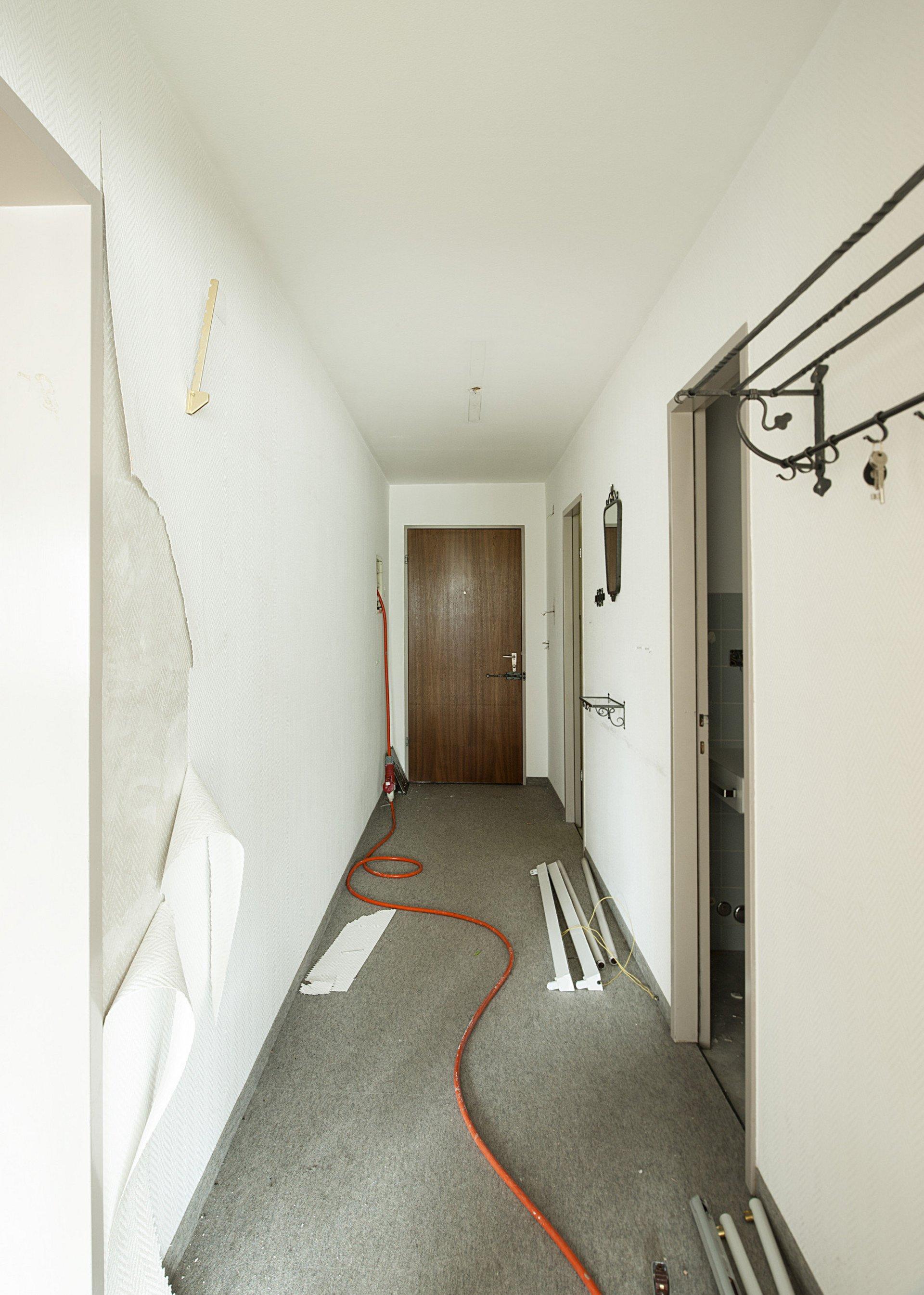 alter Flur mit grauem Teppichboden und dunkler Holztüre im Umbau