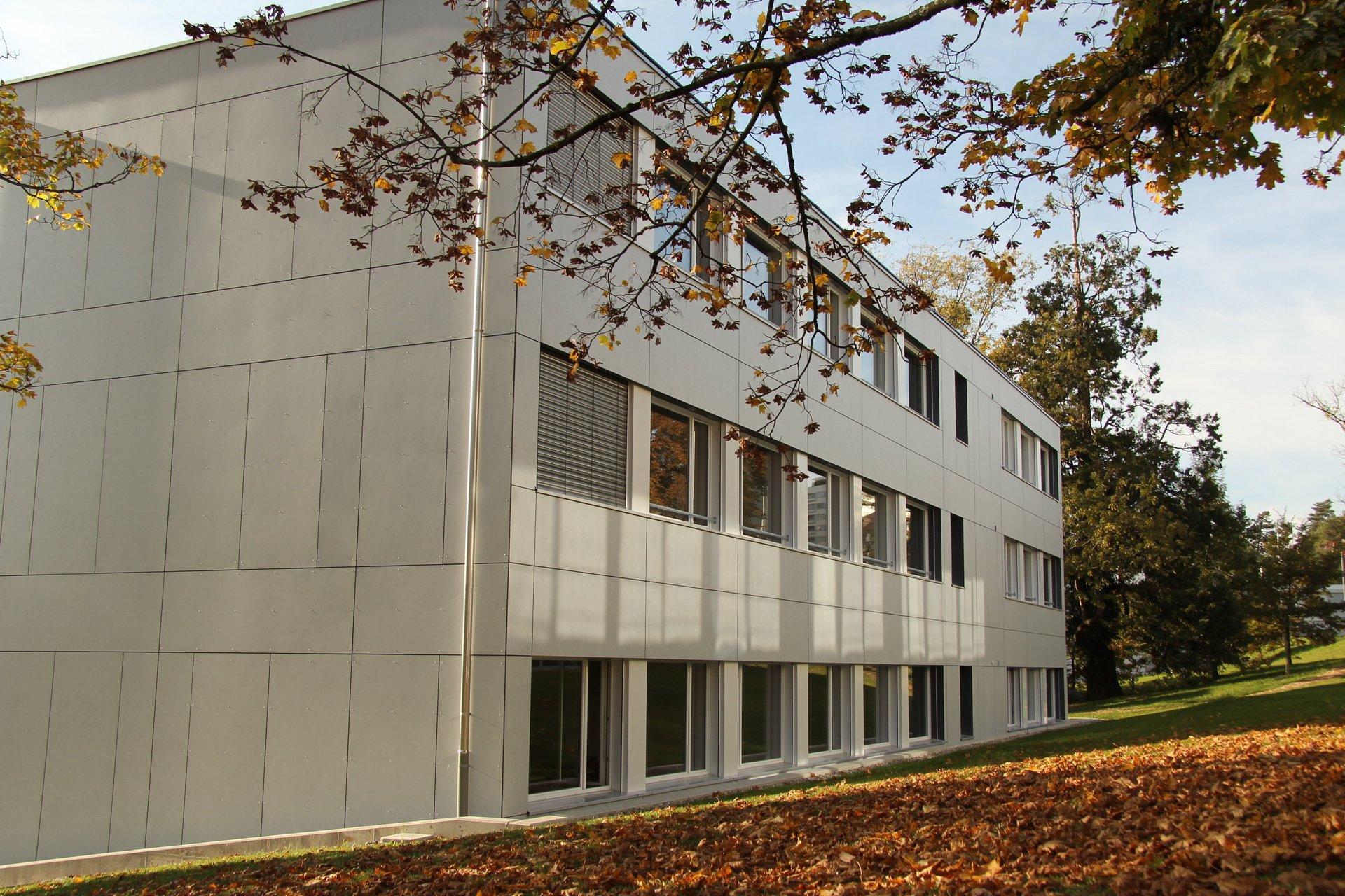 3-geschossiges Schulgebäude mit grauer Fassade