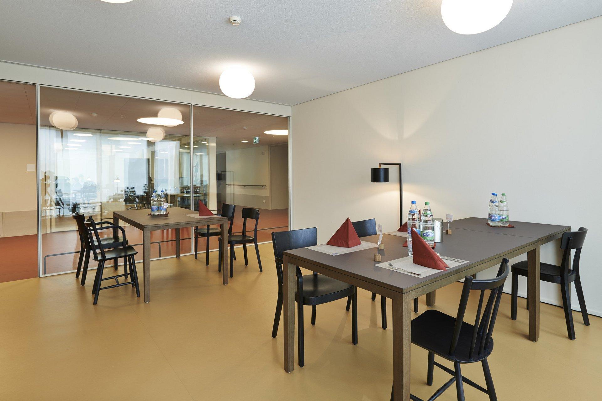 Raum mit Garnitur und lichtspendender Glaswand zum Flur hin