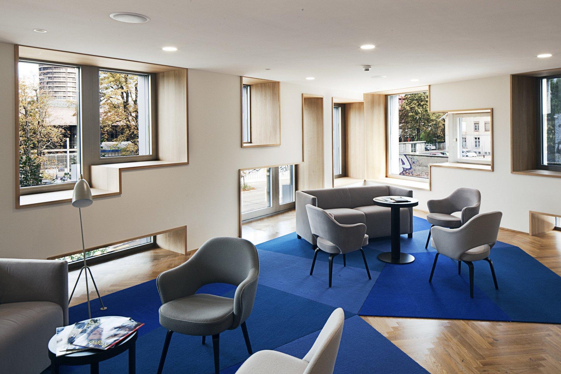 Möbilierter Raum mit geometrischen Fenstern als grosse Lichtquelle