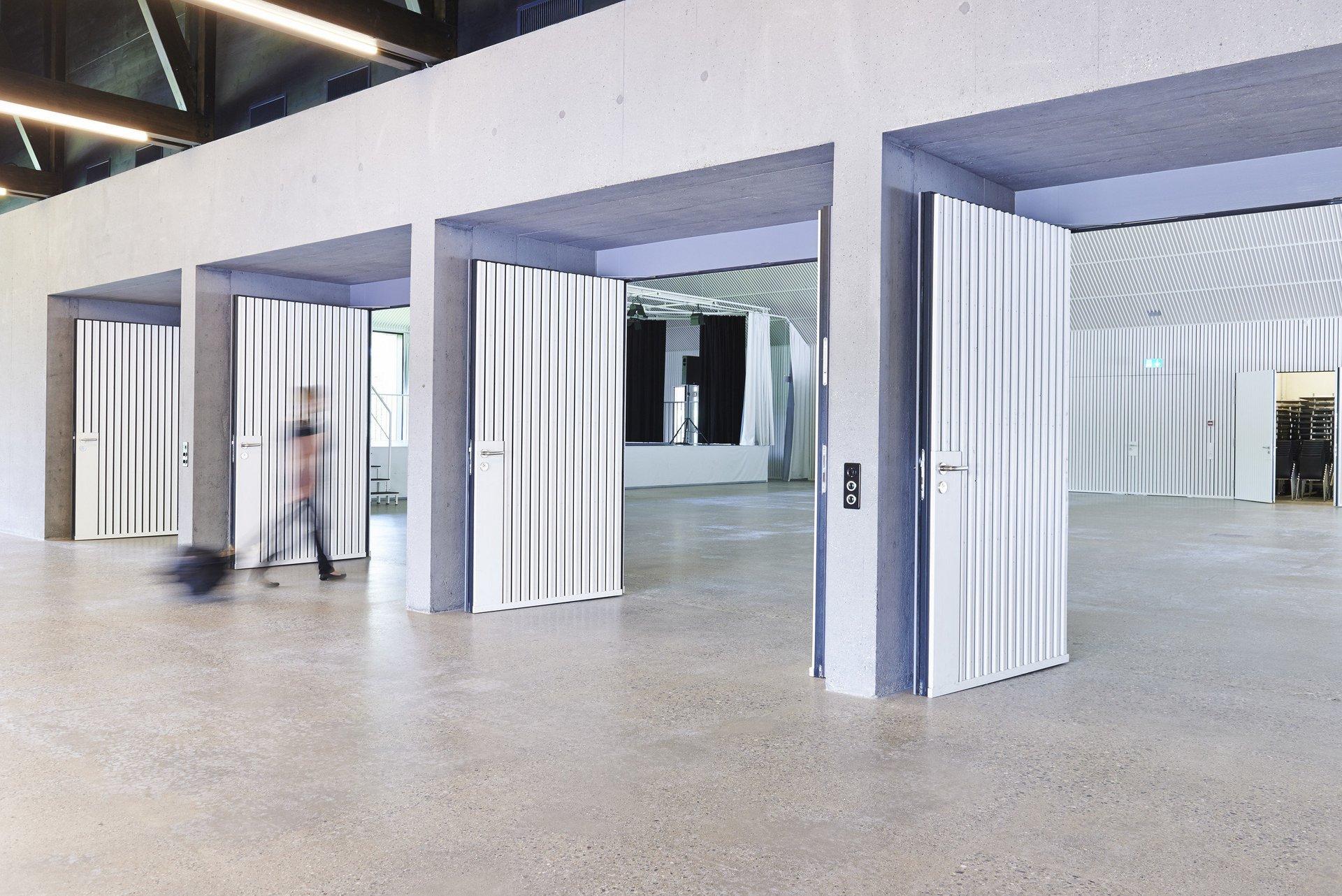 3 Brandschutztüren offenstehend in eine Halle führend in hellem Design
