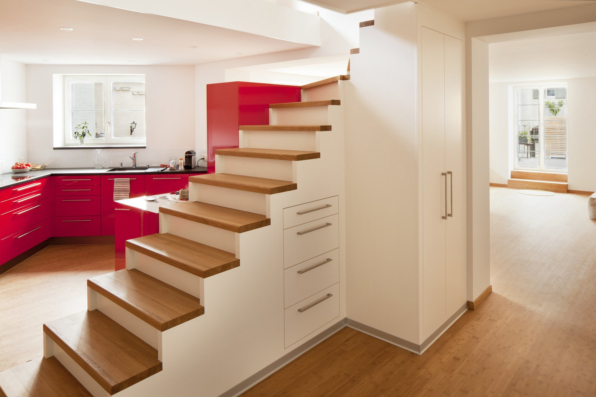 Rote Einbauküche hinter nach oben führende Treppe ohne Geländer in hellem Design