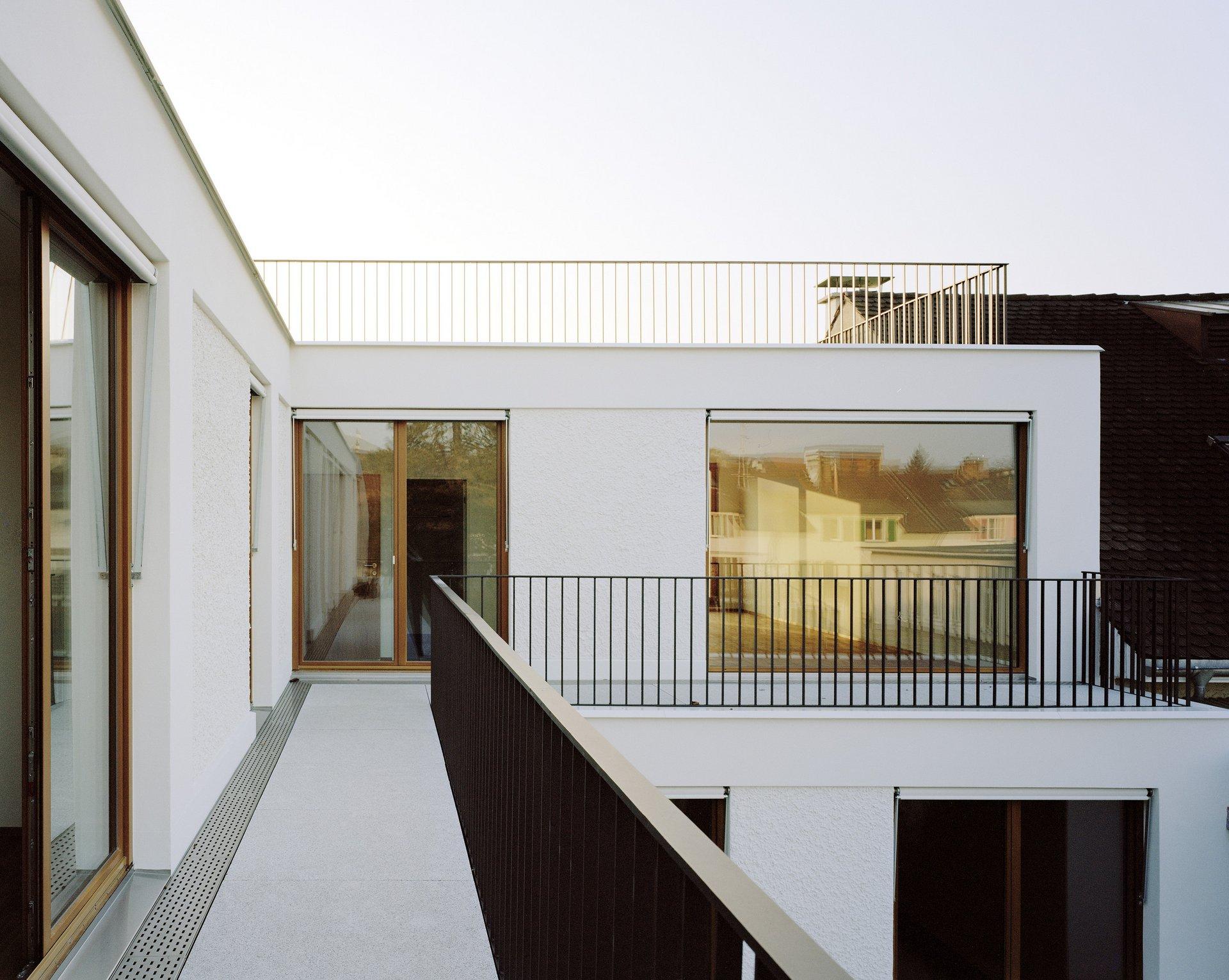 Sicht von abzweigender Terrasse mit schwarzem Geländer auf Hebe-Schiebetür aus Kiefer natur