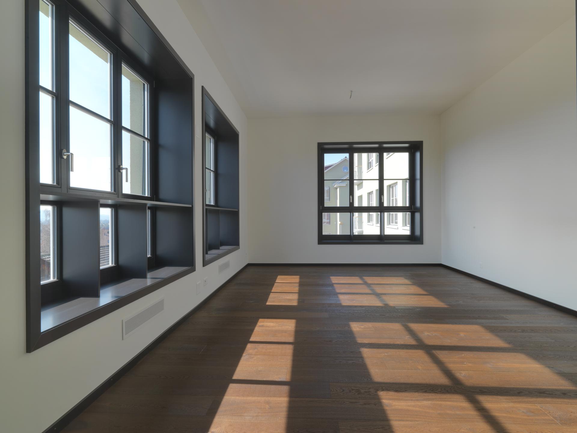 Lichtdurchfluteter Raum durch grosse Sprossenholzfenster in schlichtem Design