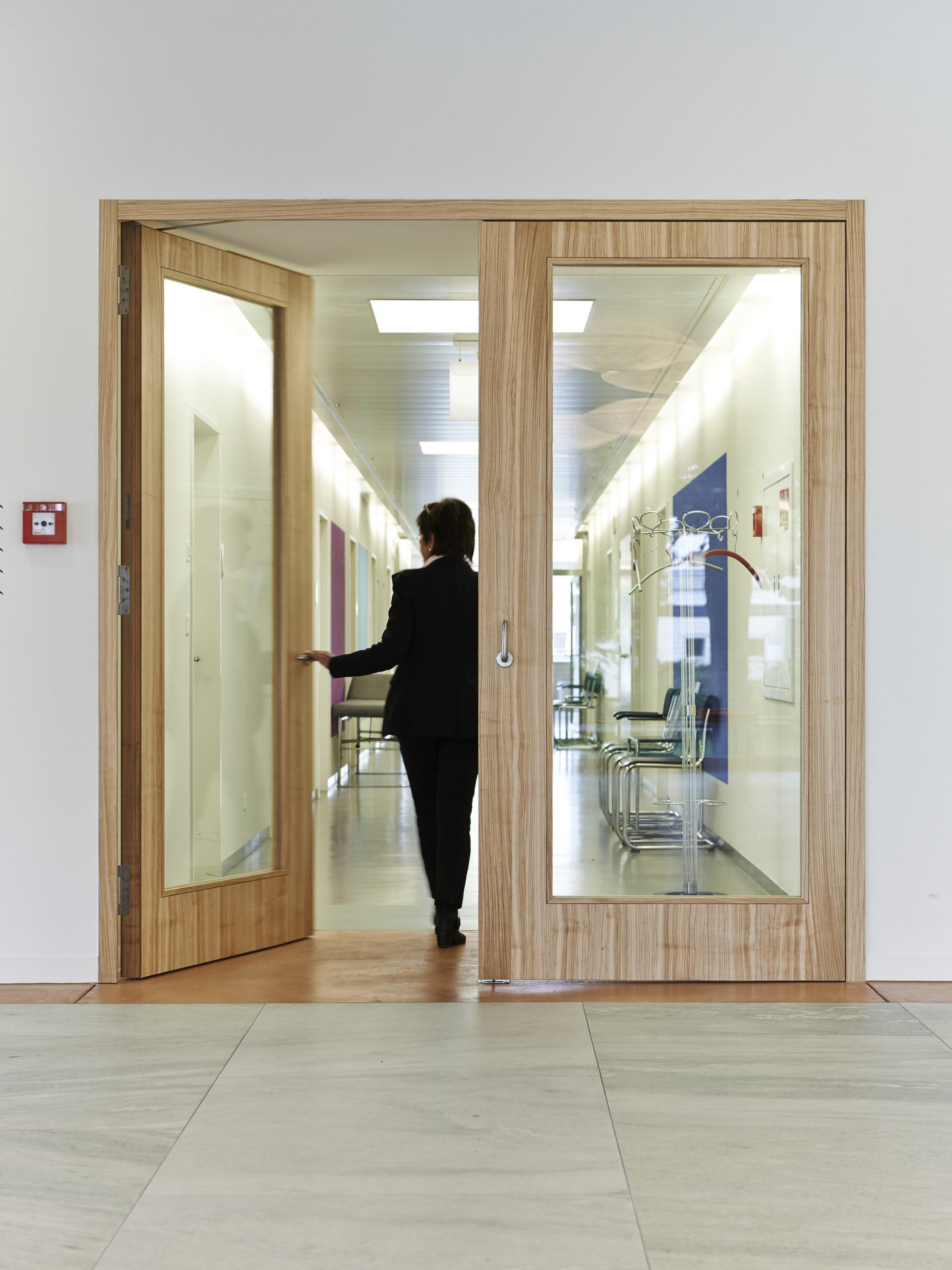 Brandschutztür Holz mit Glasfenster linke Tür offen Frau von hinten