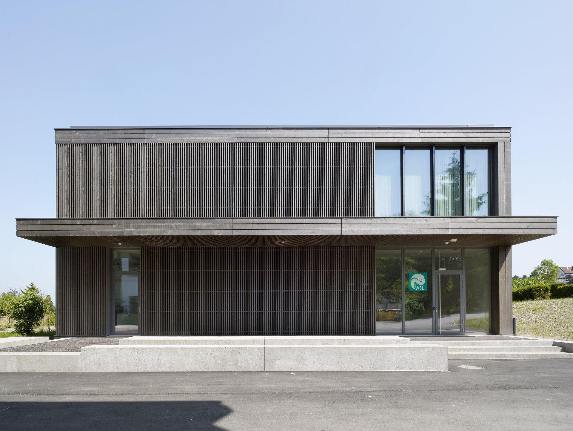Laborgebäude mit einer Holzfassade aus vertikalen Lamellen, vorvergraut
