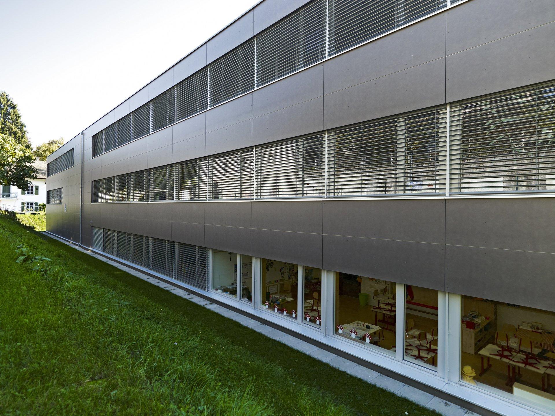 Bâtiment scolaire de 3 étages à façade de fenêtres généreuse