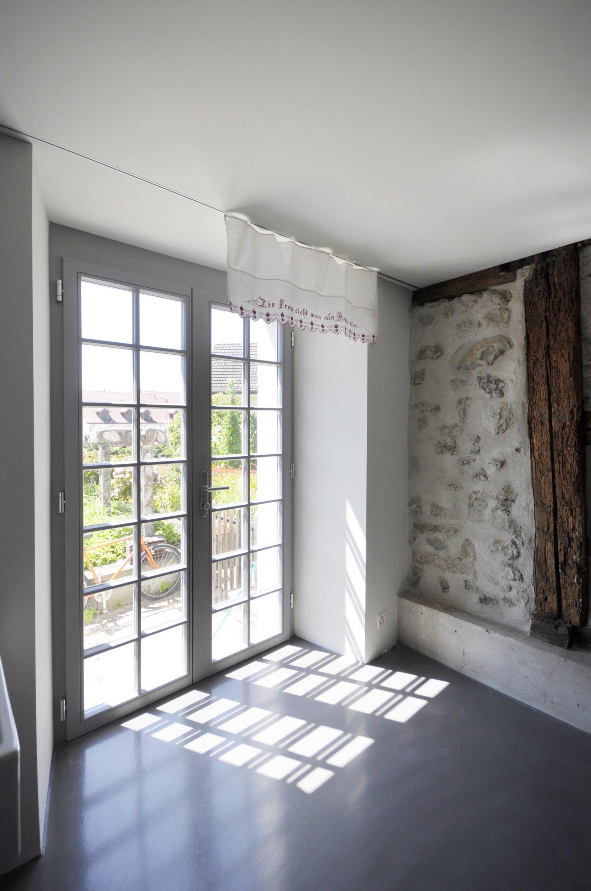 Renovierter Eingangsbereich mit Sprossenfenstertür und alter Steinwand mit Holzbalken