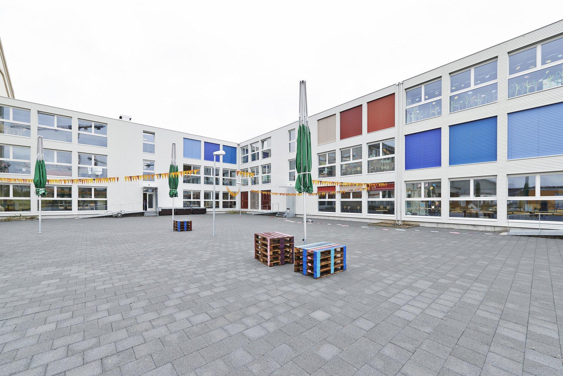 3-geschossiger Schulpavillon in weiss in Modulbauweise mit roten und blauen Jalousien