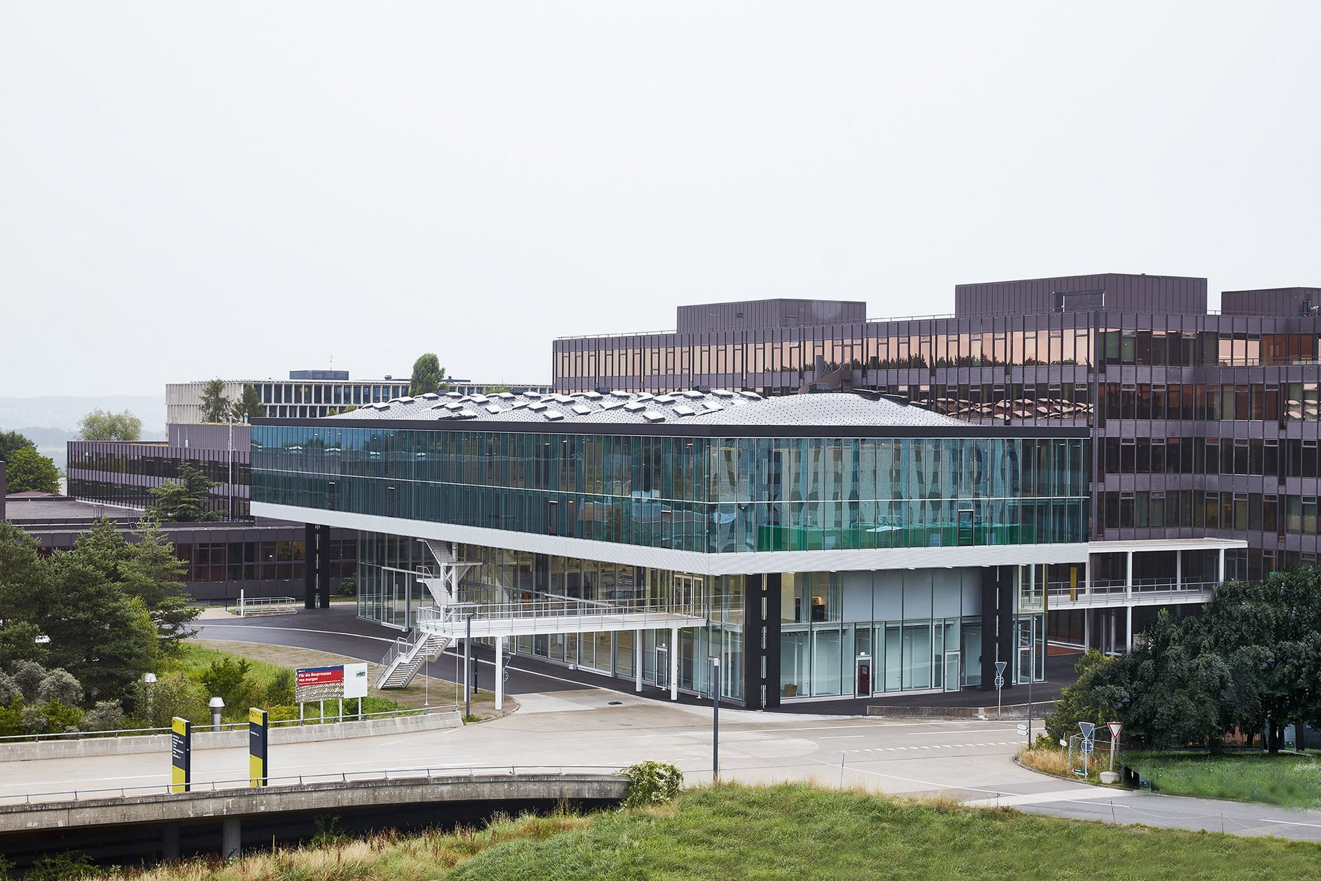 2-geschossiges Gebäude mit Fensterfassade und gewölbtem Dach