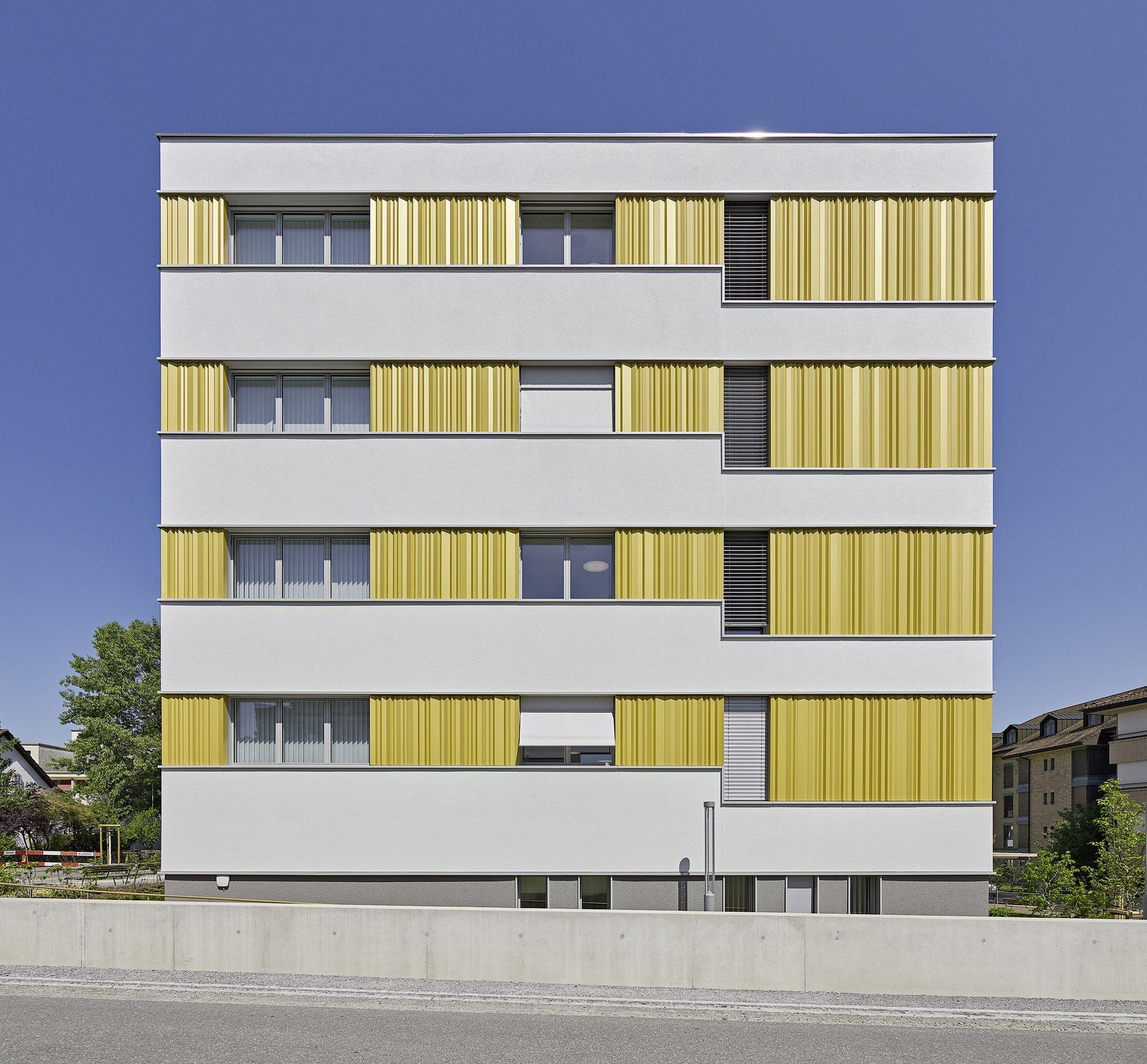 Einflügelfenster verschieden gross in gelber Fassadenkonstruktion