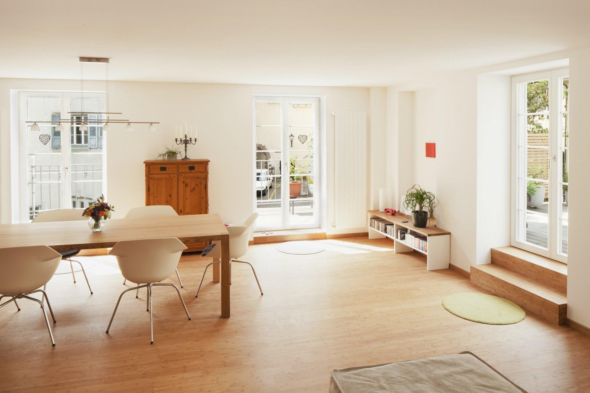 Modern möbliertes Zimmer mit Esstisch und lichtspendenden Altstadtfenstern