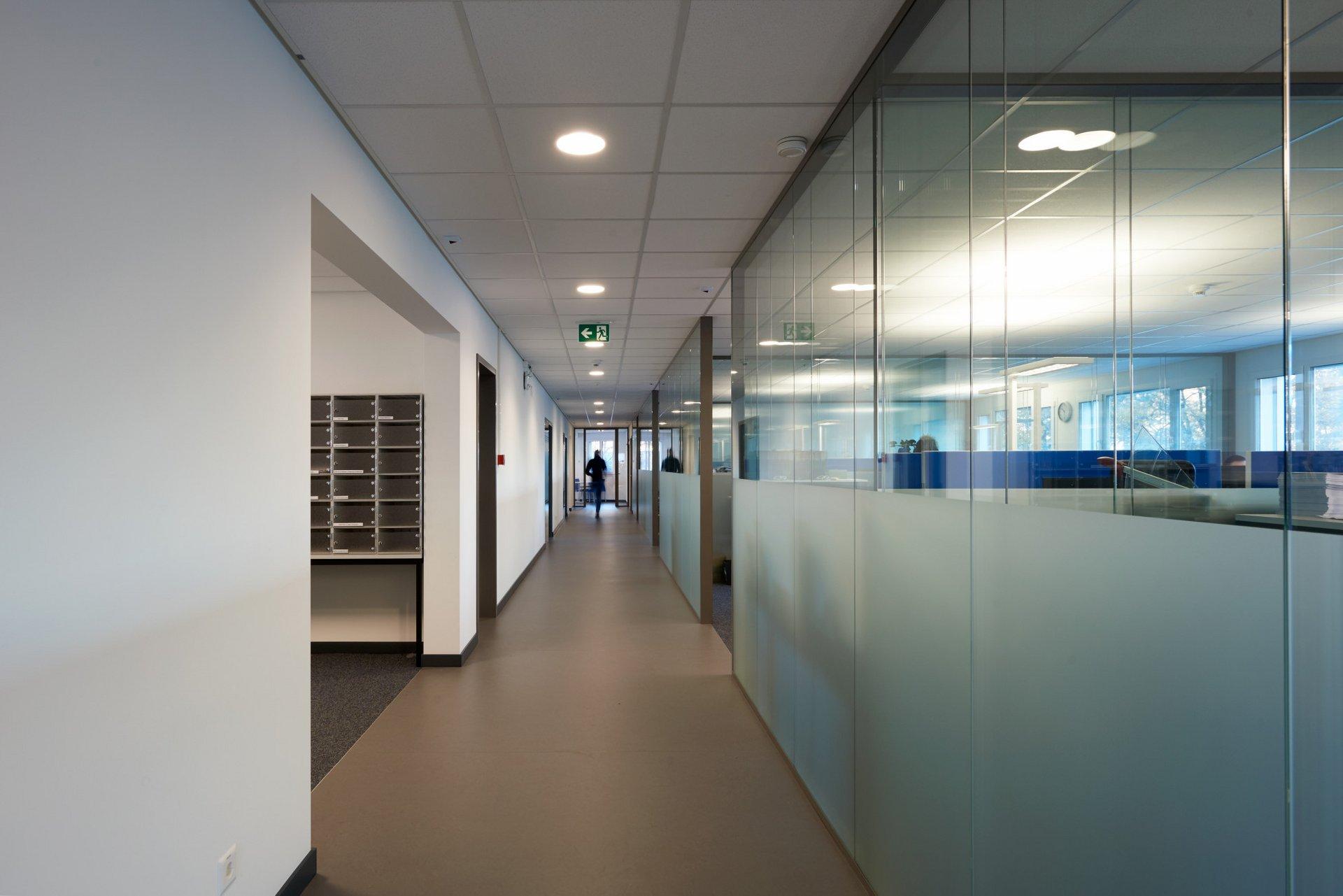 Blick auf den Flur welche rechts über viele Büros mit gläsernen Trennwänden verfügt und Links über den Ausgang