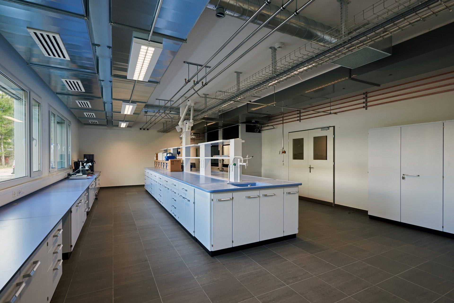 Blick in ein Raum für Forschungszwecke, metallene Belüftungsschächte zieren die Decke und spiegeln sich im darunterliegenden dunkelbraunen Steinboden