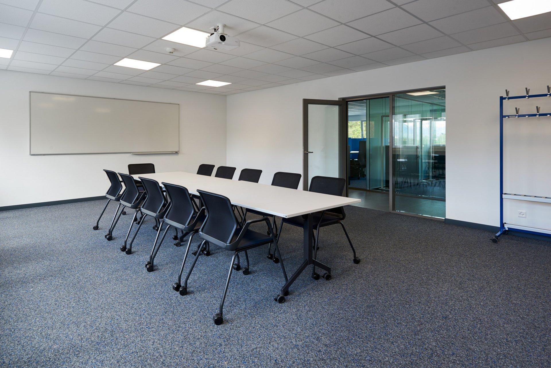 Einblick in ein Sitzungszimmer mit rollbaren Stühlen und Tischen, einem grossen Whiteboard und einem grauen Teppich