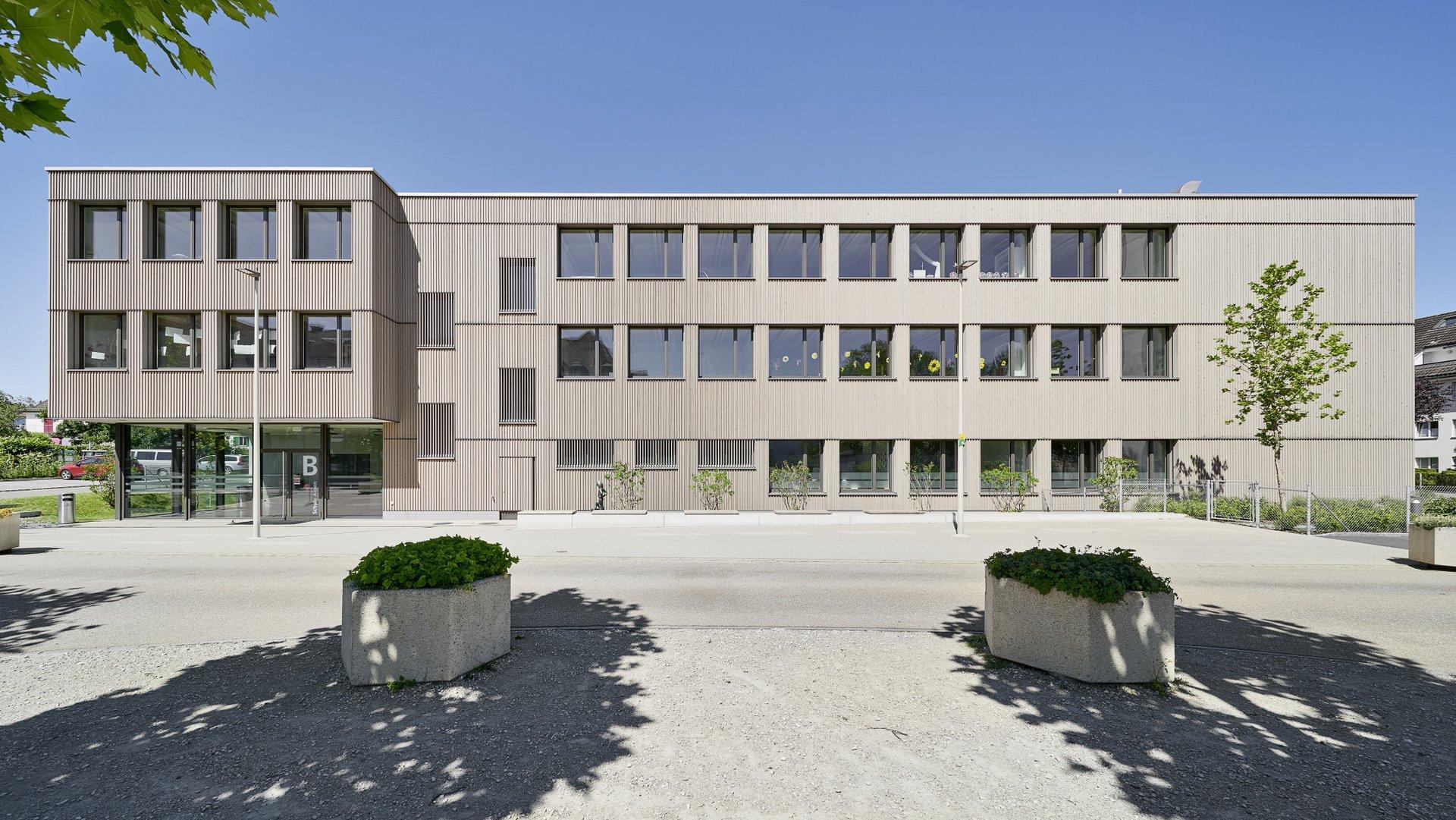 Sicht auf den Eingangsbereich eines Schulhauses mit einer sandbraunen Betonfassade