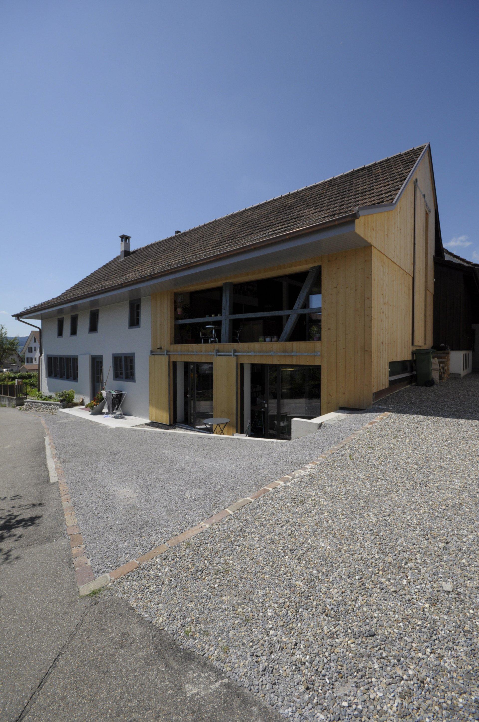 Aussenansicht von 2-geschossigem Haus mit neuer Holzfassade und grosszügiger Fensterfläche