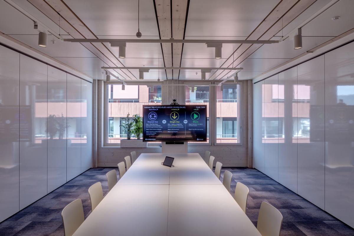 Moderner Besprechungsraum mit langem Tisch und grossem TV Bildschirm