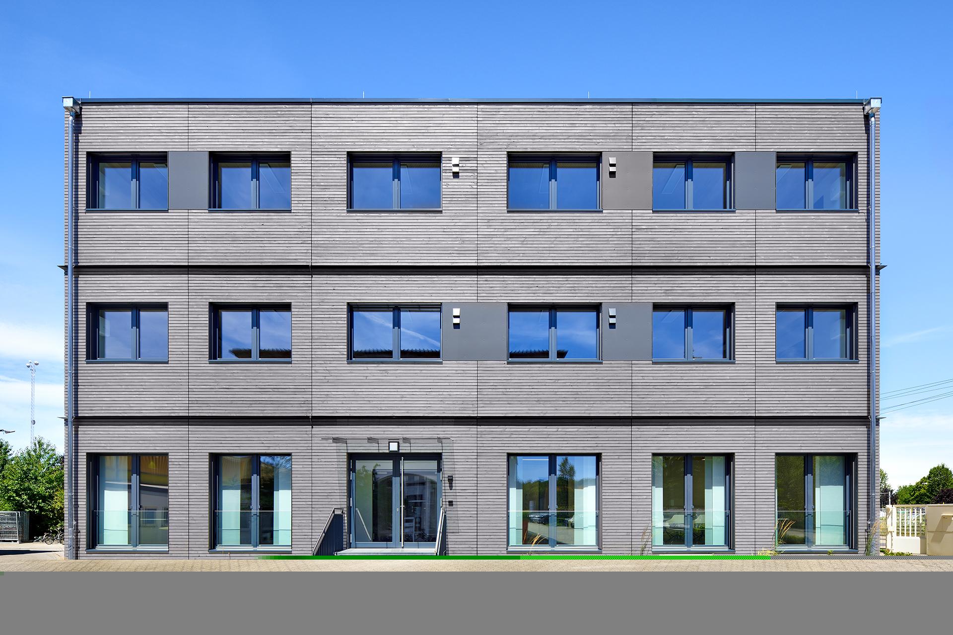 Graue Fassade mit blau schimmernden Fenstern eines Bürogebäudes in Modulbauweise