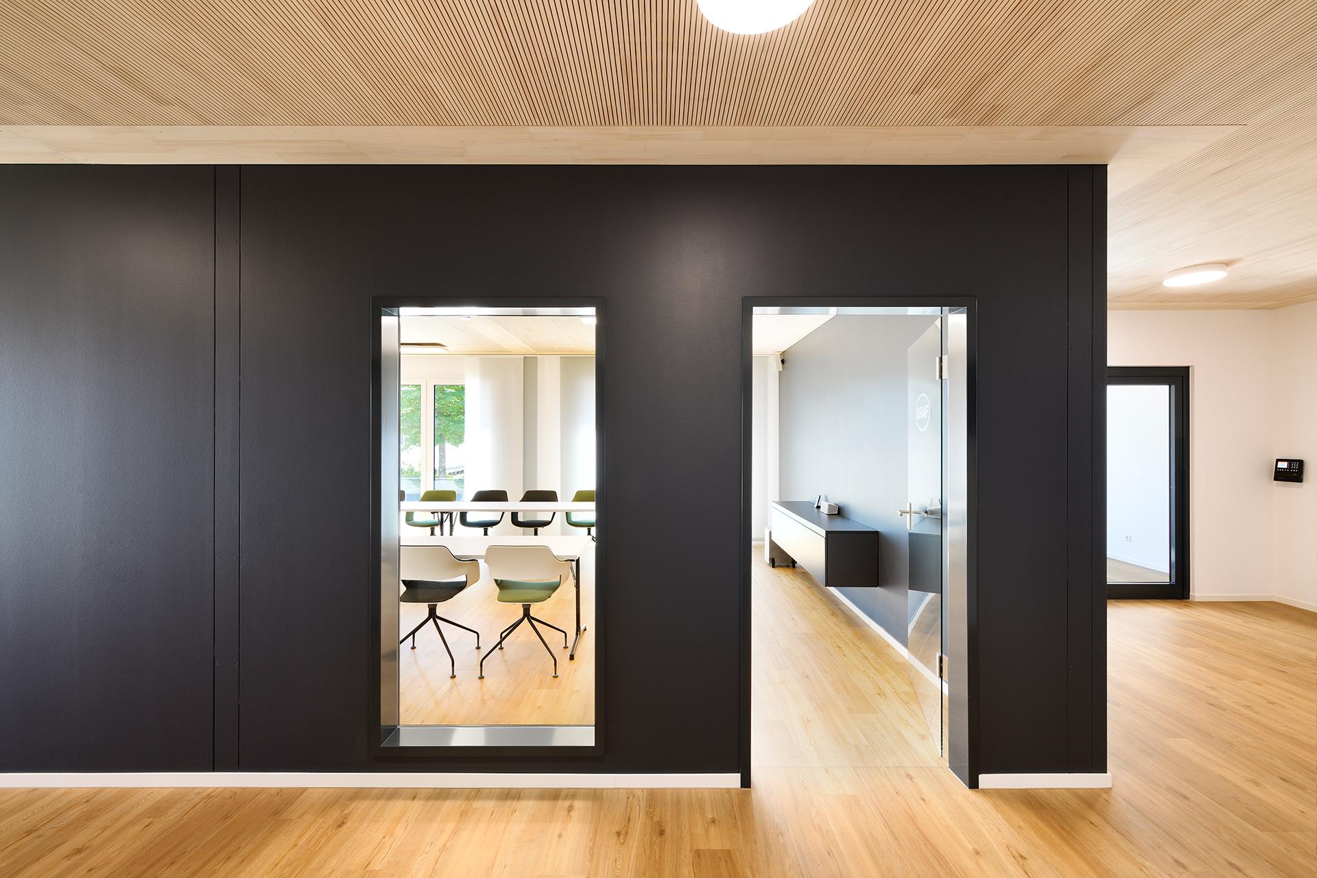 Eingang zum Sitzungszimmer in einer schwarzen Trennwand mit Fenster und Glastüre