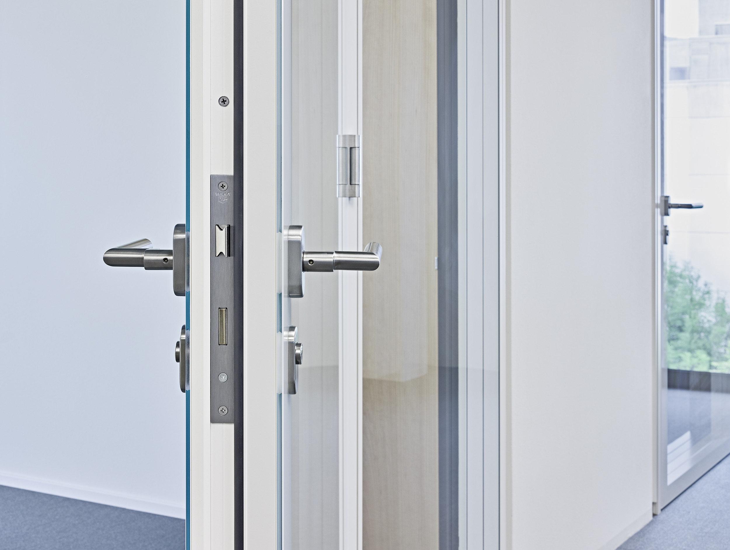 Fokus auf modernen silbernen Türgriff einer Brandschutztür mit Fensterteil