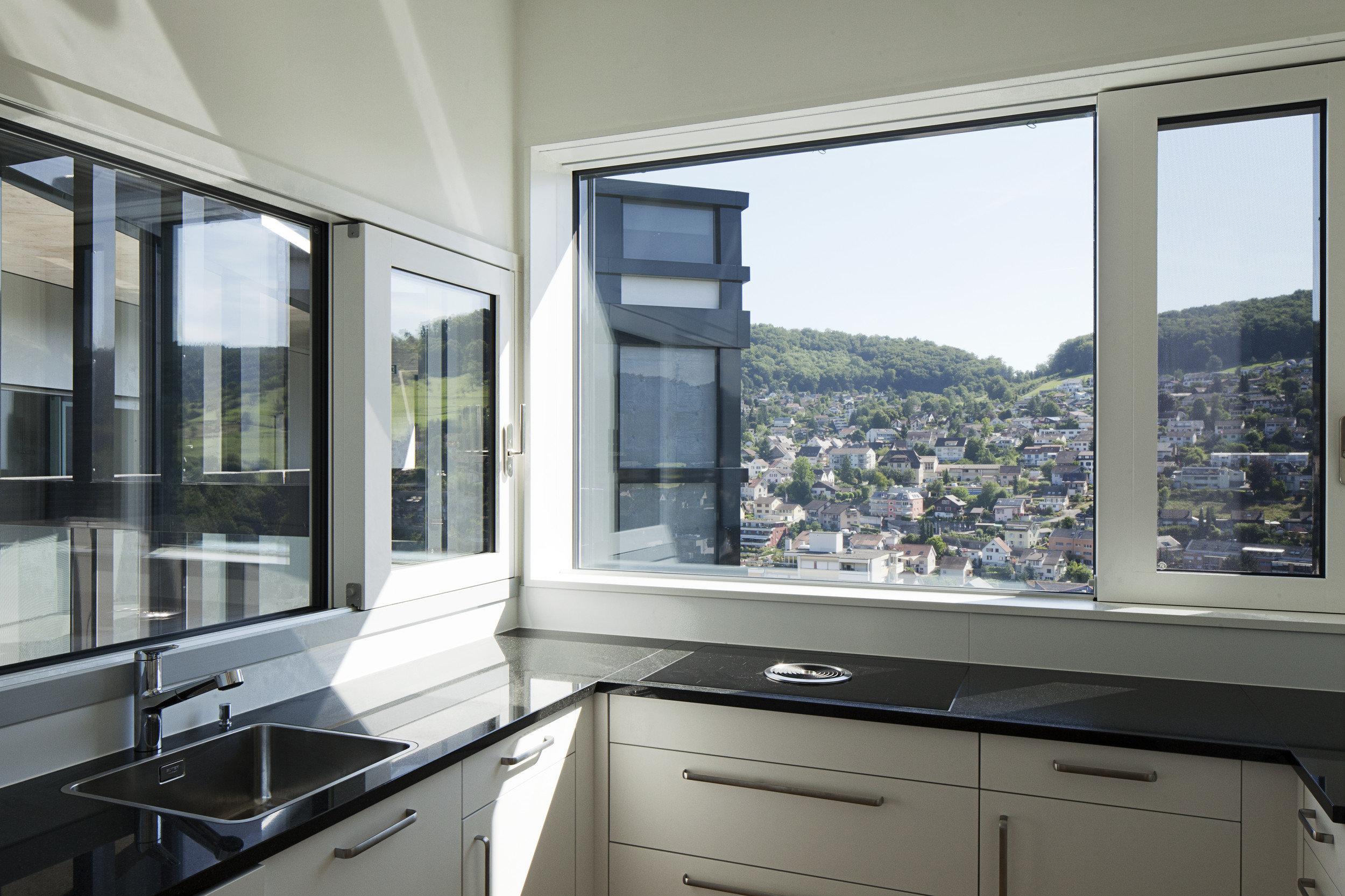 Einbauküche mit grosser Fensterfront in schlichtem und modernem Stil