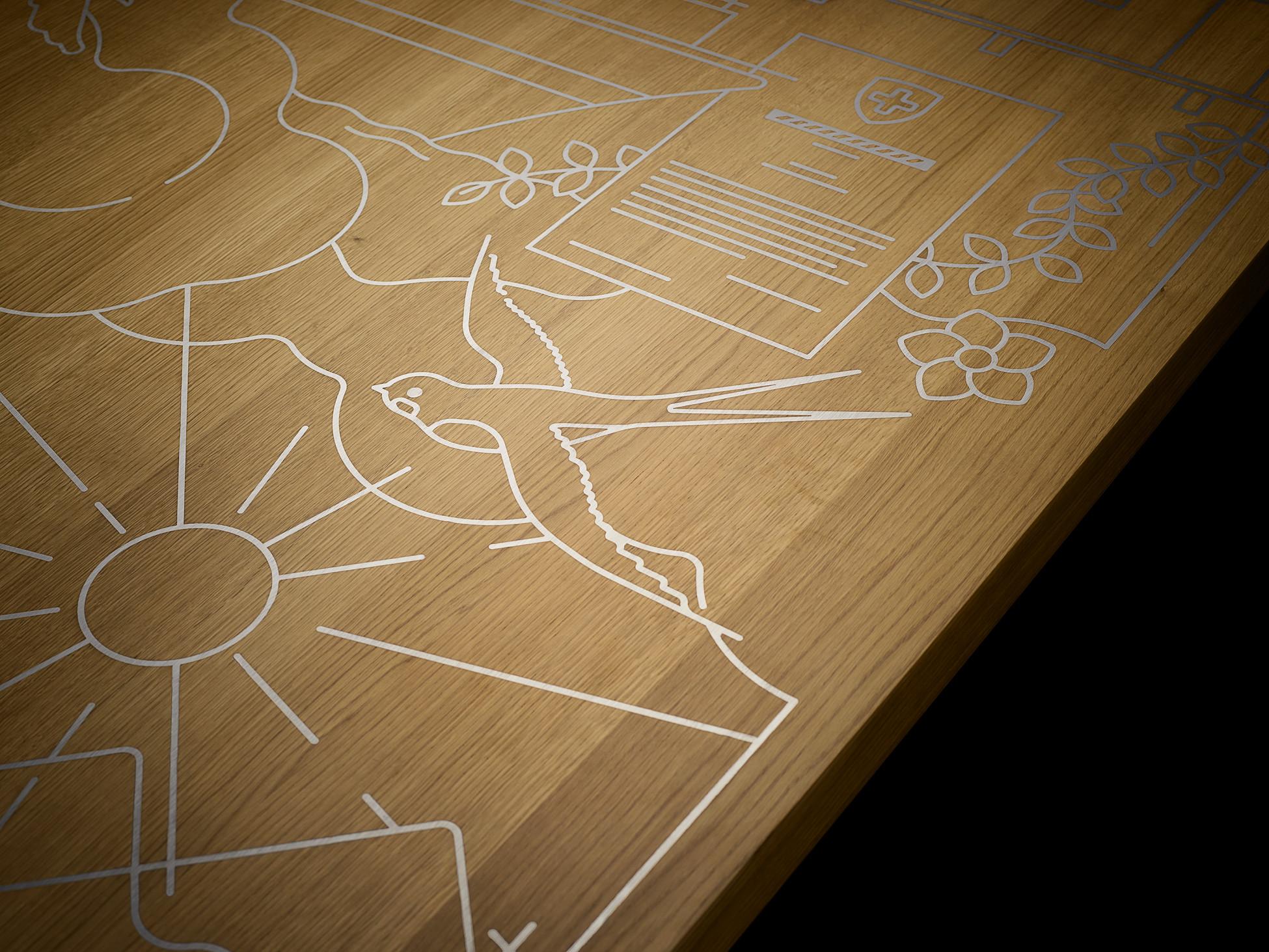Detailansicht eines Holztisches mit eingravierter Firmengeschichte mit Zinnguss