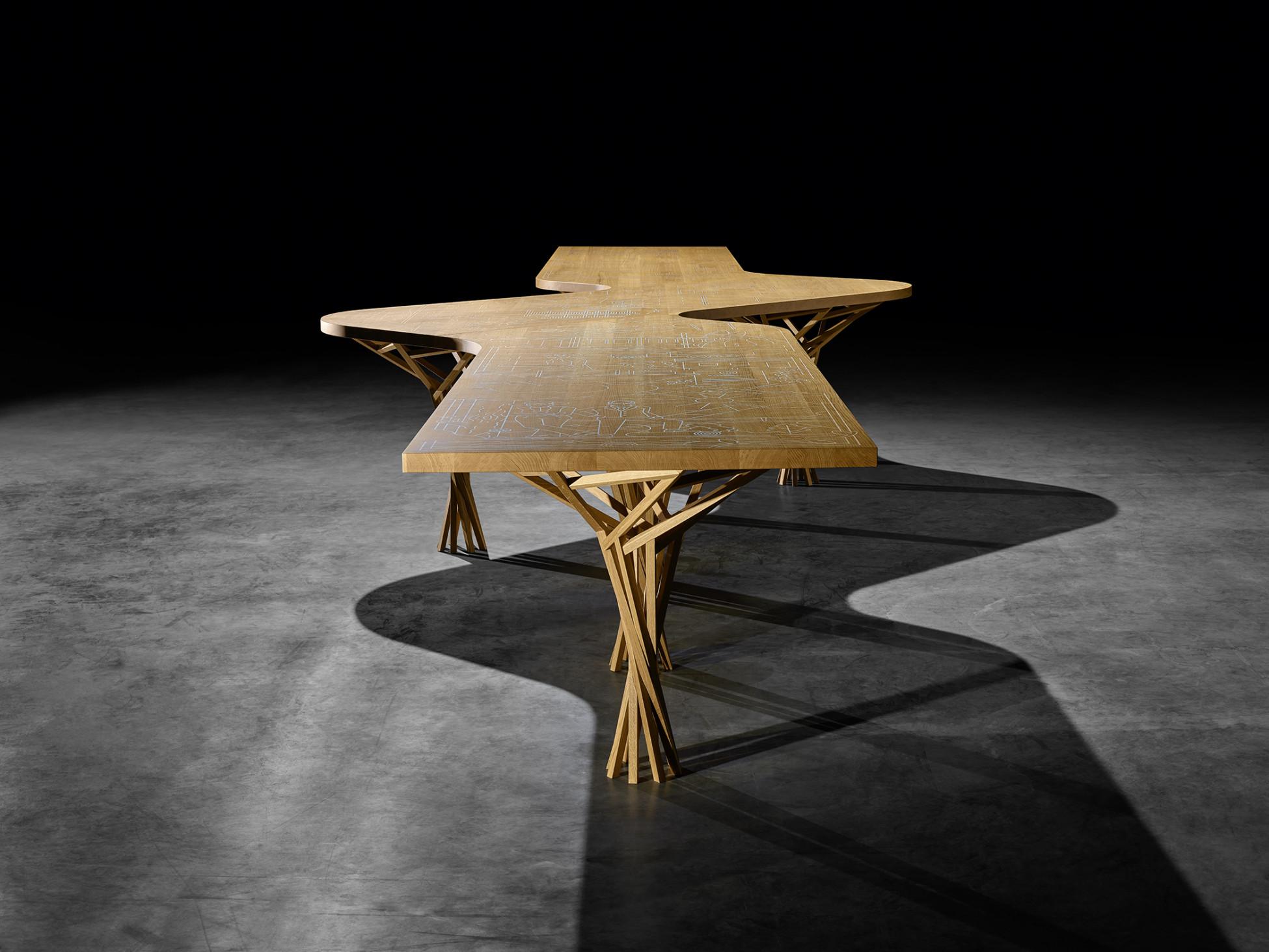Langer Holztisch mit eingravierter Firmengeschichte und filigranen Holzbeinen parametrisch designet