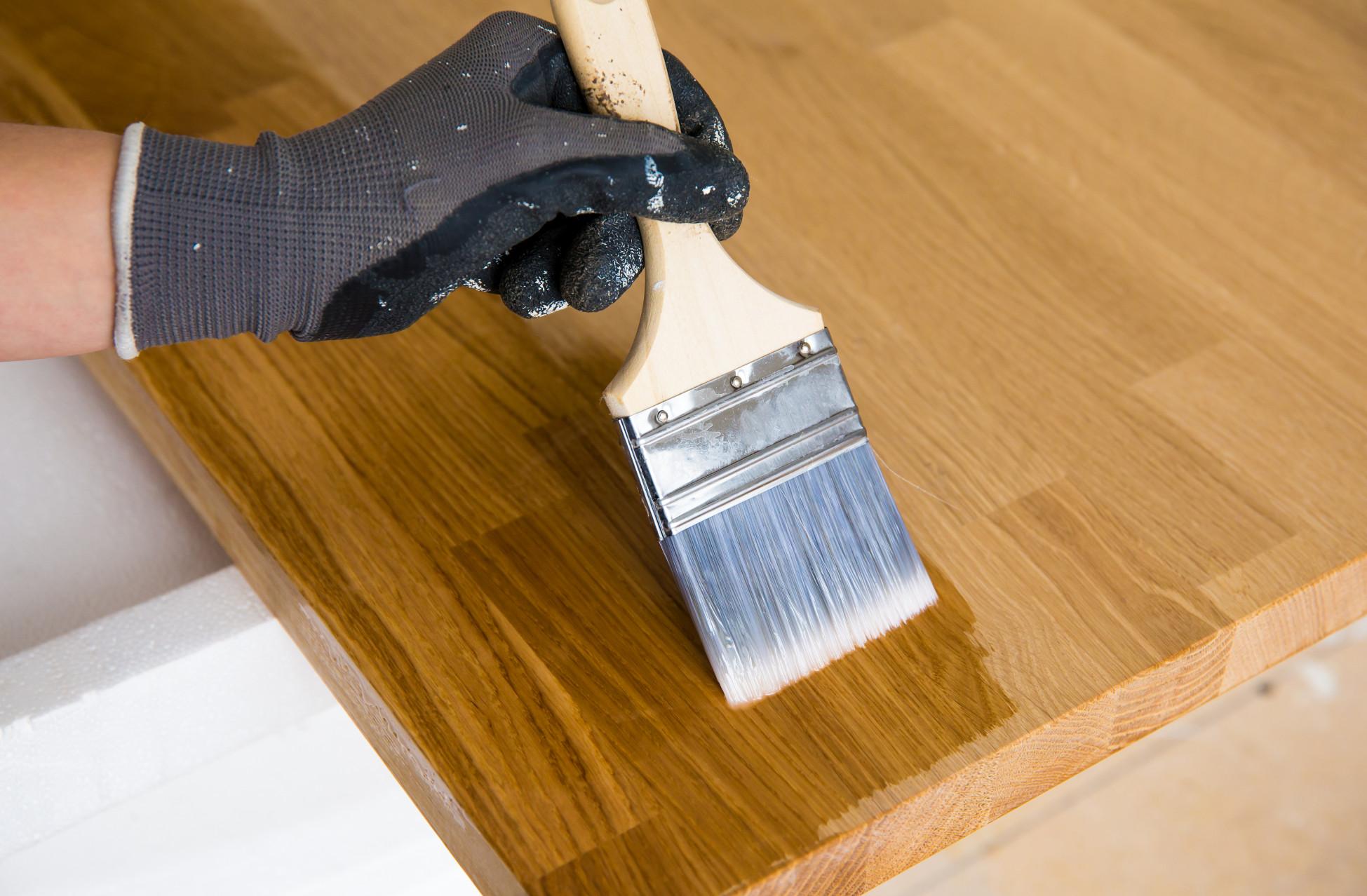 Nahaufnahme einer Hand die ein Stück Holz mit einem grossen Pinsel lasiert