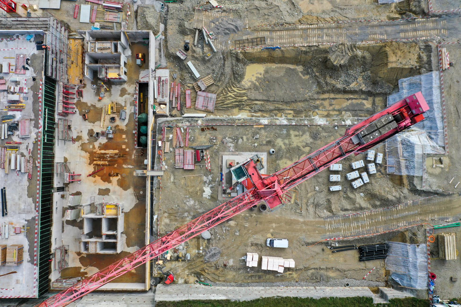 Baustelle mit rotem Kran aus der Vogelperspektive